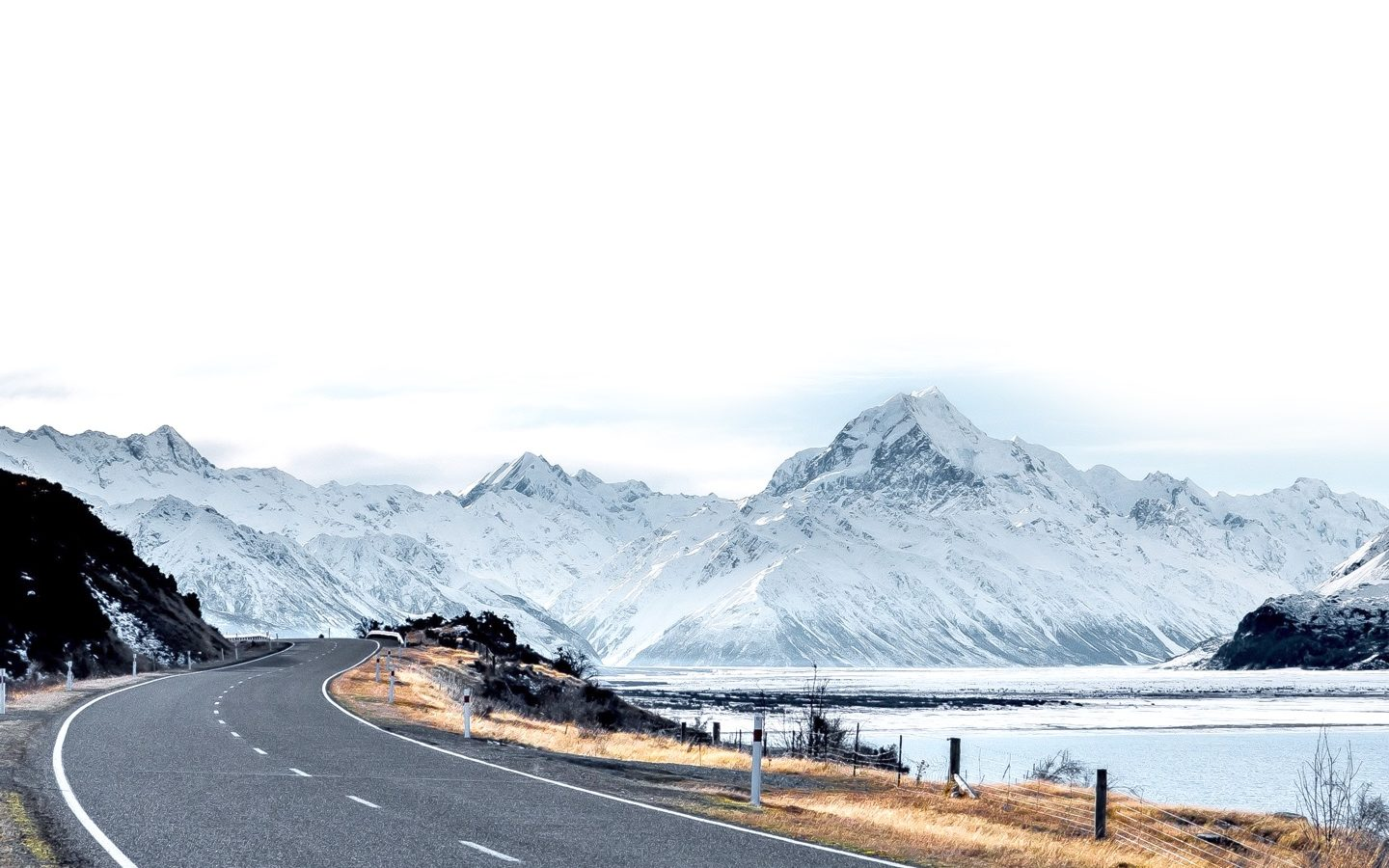 winding road with snowy mountains behind